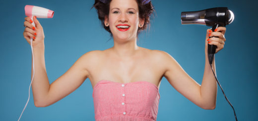 Young woman preparing to party having fun, funny girl styling hair with two hairdreyers retro style on blue