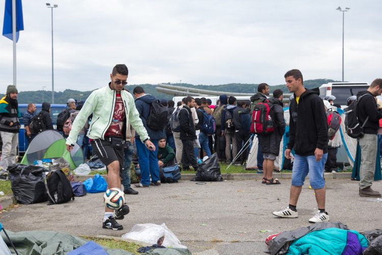BREGANA, SLOVENIA: SEPTEMBER 19, 2015: Group of immigrants and refugees from Middle East and North Africa at Bregana, state border between Slovenia and Croatia. Man talking with police behind barrier